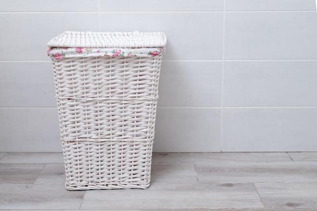 Cesto della biancheria in vimini bianco nella lavanderia.