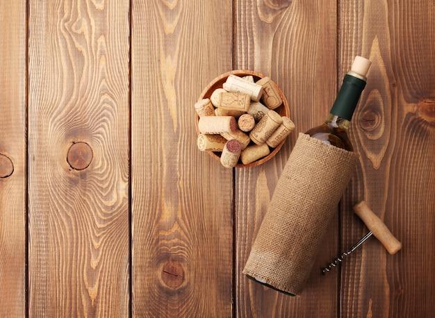Bottiglia di vino bianco, ciotola con tappi di sughero e cavatappi. vista dall'alto sullo sfondo del tavolo in legno rustico