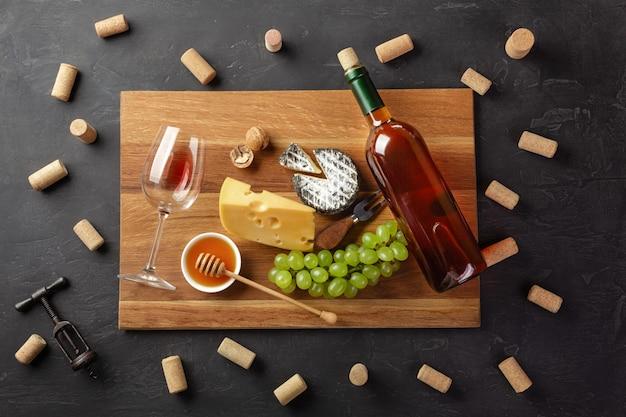 Bottiglia di vino bianco, testa di formaggio, grappolo d'uva, miele, noci e bicchiere di vino sul tagliere con tappi di sughero e cavatappi