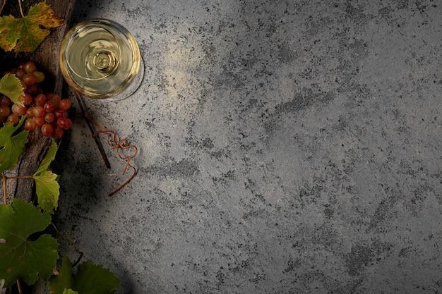 Vino bianco in un bicchiere, uva e rami d'uva sul tavolo. vista dall'alto. copia spazio per il tuo testo.