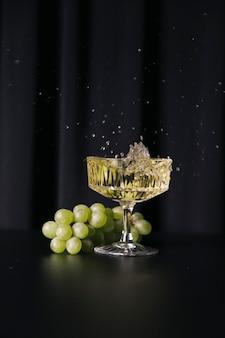 Vino bianco e uva su fondo scuro