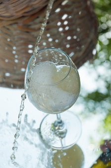 Il vino bianco viene versato oltre il bicchiere. cornice verticale
