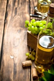 Vino bianco con una cassa piena di uva. su un tavolo di legno.