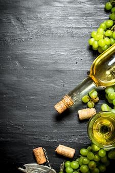 Vino bianco con rami d'uva. su uno sfondo di legno nero.