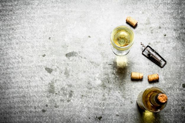 Vino bianco con tappi di sughero. sul tavolo di pietra.