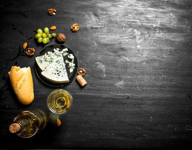 Vino bianco con formaggio blu francese e noci. sulla tavola di legno nera