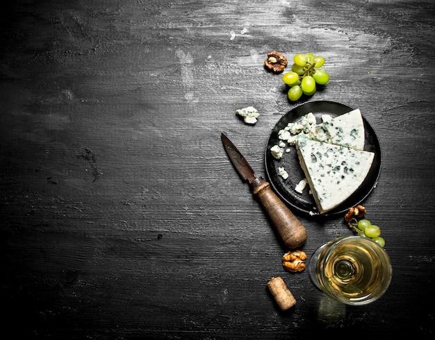 Vino bianco con una fetta di formaggio con muffa blu. su un tavolo di legno nero.
