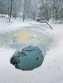 Paesaggio invernale bianco con ristagno rotondo e ghiaccio sul fiume. vista verticale.