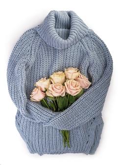 Maglione invernale bianco con un mazzo di fiori, rose delicate, adagiato su una superficie bianca Foto Premium