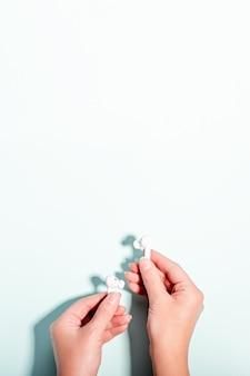 Auricolari senza fili bianchi in mano femminile su fondo pastello, spazio della copia. tecnologia moderna piatta con auricolari cordless in mano donna, concetto di stile di vita moderno, vista dall'alto