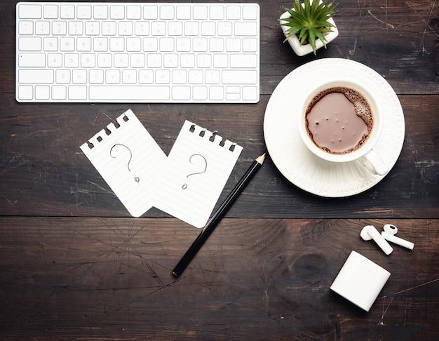 Tastiera wireless bianca e tazza di caffè su un tavolo in legno marrone, vista dall'alto, sul posto di lavoro