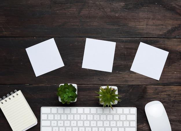 Tastiera e mouse wireless bianchi su un tavolo in legno marrone, accanto a tre fogli di carta bianchi vuoti, vista dall'alto, copia dello spazio