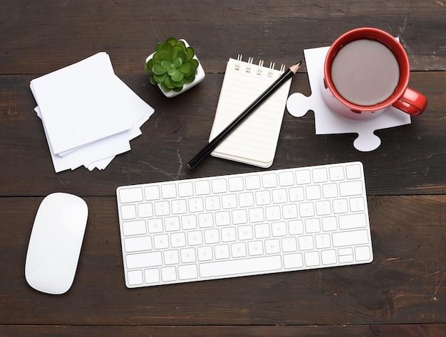 Tastiera e mouse senza fili bianchi sulla tavola di legno marrone, vista dall'alto, posto di lavoro