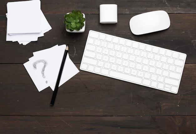 Tastiera e mouse wireless bianchi su un tavolo in legno marrone, vista dall'alto, sul posto di lavoro