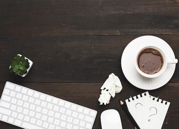 Tastiera e mouse wireless bianchi su un tavolo in legno marrone, accanto a una tazza bianca con caffè, vista dall'alto