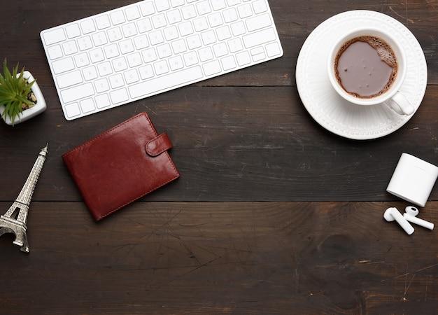 Tastiera wireless bianca e cuffie wireless e portafoglio in pelle marrone sul tavolo in legno marrone, accanto a una tazza bianca con caffè, vista dall'alto