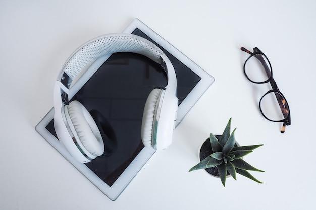 Wireless bianco su una tavoletta bianca, occhiali e un fiore su un tavolo bianco. wilde in cima. concetto di podcast, audiolibri, apprendimento online.