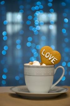 Bianco con tazza d'argento di cioccolata calda con marshmallow e biscotto cuore con parola d'amore su luci bokeh blu