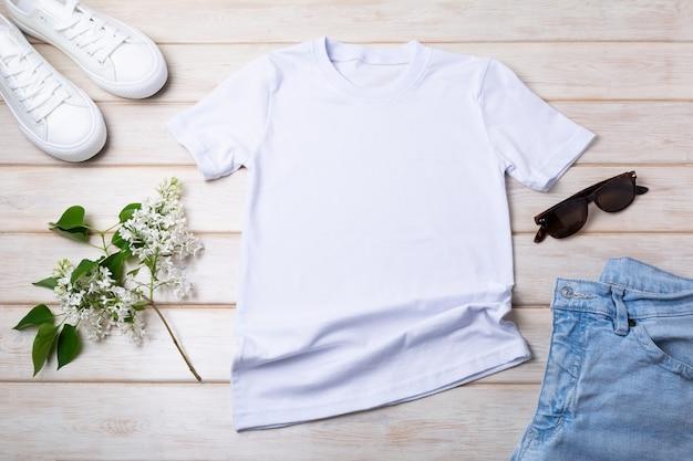 Mockup di t-shirt in cotone da donna bianca con lilla, blue jeans, scarpe sportive e occhiali da sole. modello di maglietta di design, presentazione di stampa t-shirt mock up