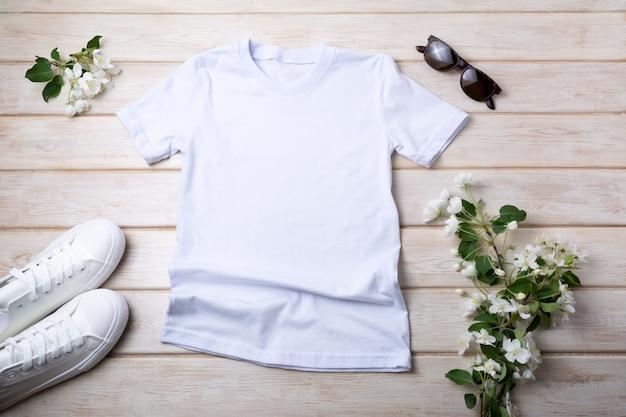 Mockup di t-shirt in cotone da donna bianca con scarpe da ginnastica, occhiali da sole e fiori di melo. modello di maglietta di design, presentazione di stampa t-shirt mock up
