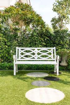 Presidenza di banco di legno bianca con il cespuglio priorità bassa in giardino a casa.