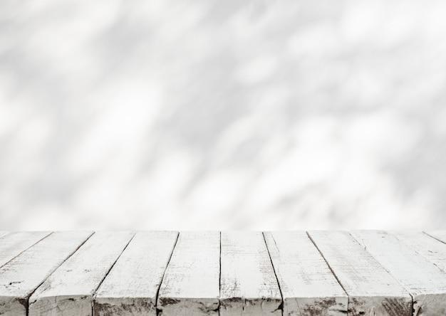Piano tavolo in legno bianco con ombra di foglia d'albero sul fondo della parete.per l'esposizione del prodotto e il concetto naturale
