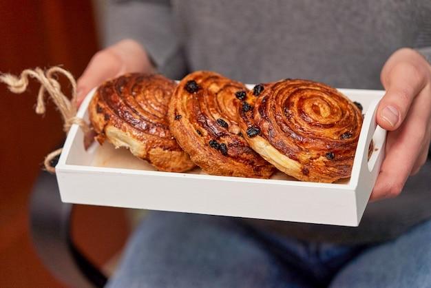 Scatola di legno bianca con panini con uvetta in mani femminili