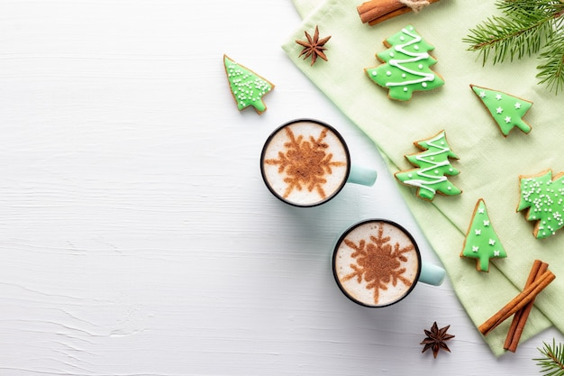 Sfondo di natale in legno bianco con biscotti a forma di albero con glassa e latte decorato da fiocchi di neve