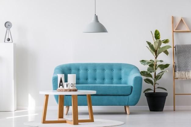 Tavolino da caffè in legno bianco accanto al divano elegante blu nell'interno luminoso del soggiorno con pianta in vaso nero e scala scandinava