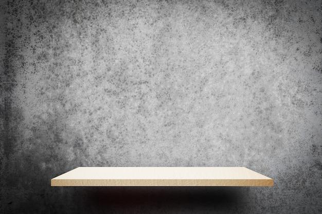 Scaffale vuoto di legno bianco sul fondo grigio della parete per l'esposizione del prodotto