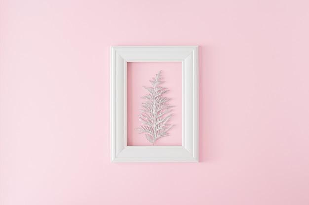 Cornice in legno bianco con ramo di thuja argenteo su sfondo rosa chiaro