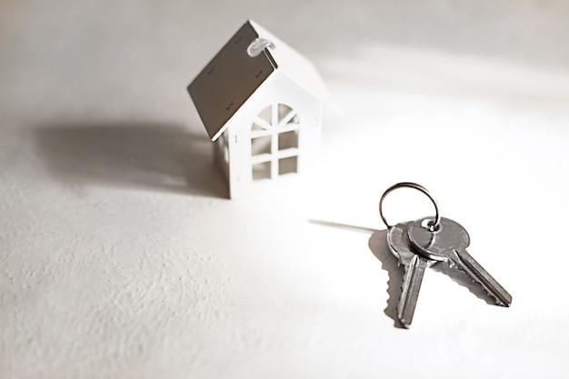 Simbolo e chiavi della casa in legno bianca su sfondo grigio