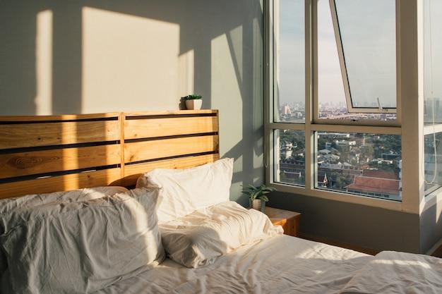 Camera da letto in stile loft bianco e legno e luce calda del sole del mattino.