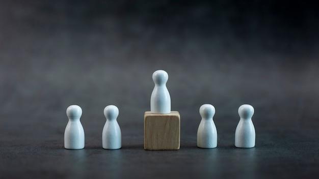 Modello di persona in legno bianco tra persone su sfondo nero
