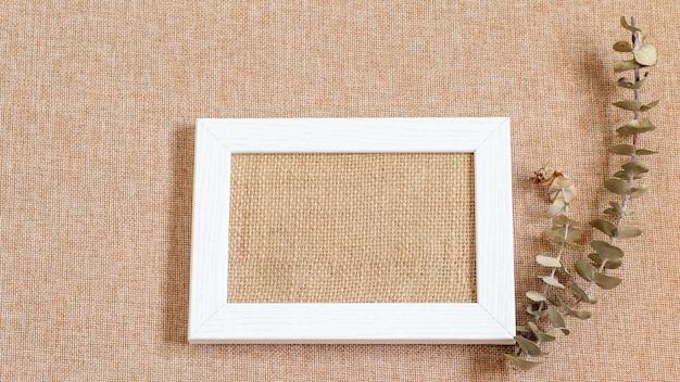 Cornice in legno bianco con vestiti di tela al centro e ramo di eucalipto per la decorazione. fondo strutturato della tela da imballaggio di lerciume.