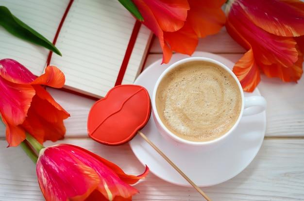 Su un tavolo di legno bianco c'è un quaderno rosso con tulipani, c'è una tazza di caffè e un pan di zenzero a forma di labbra scarlatte