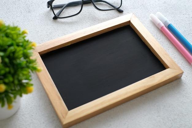 Tavolo in legno bianco con lavagna, occhiali, penna, piante decorative. vista dall'alto con copia spazio, piatto.