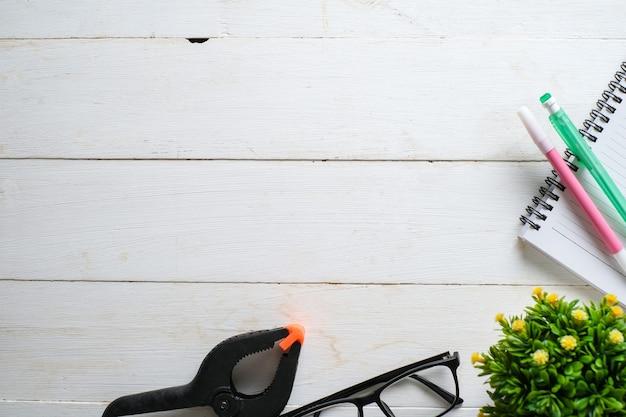 Tavolo in legno bianco con taccuino, occhiali, penna, piante decorative. vista dall'alto con copia spazio, piatto.
