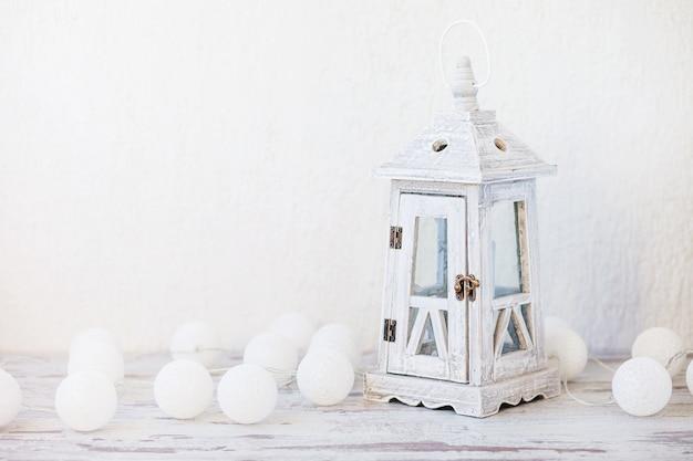 Lanterna vintage in legno bianco e palline bianche su sfondo bianco. copia spazio