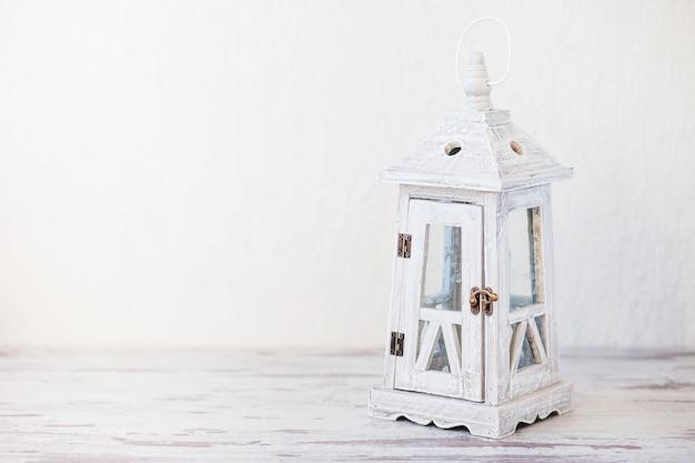 Lanterna vintage in legno bianco su bianco.