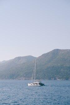 Catamarano yacht bianco con vele abbassate sul mare contro le montagne