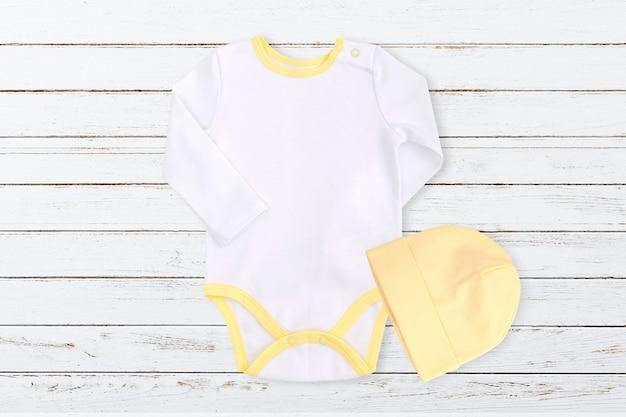 Modello di body per bebè bianco e giallo