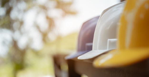 Cappello del casco di sicurezza duro bianco, giallo e blu per il progetto di sicurezza dell'operaio come ingegnere o lavoratore sul tavolo. concentrarsi sul casco bianco