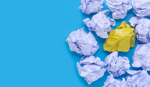 Sfere di carta sgualcite bianche e gialle su una priorità bassa blu.
