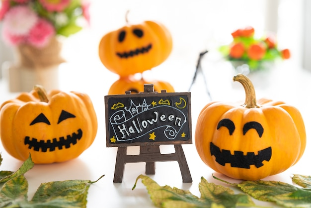 Zucche bianche e gialle del fantasma con il cappello della strega e testo felice di halloween