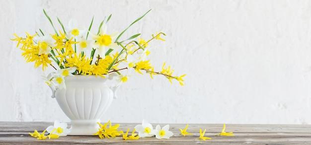 Fiori primaverili bianchi e gialli in vaso su un vecchio muro bianco di sfondo
