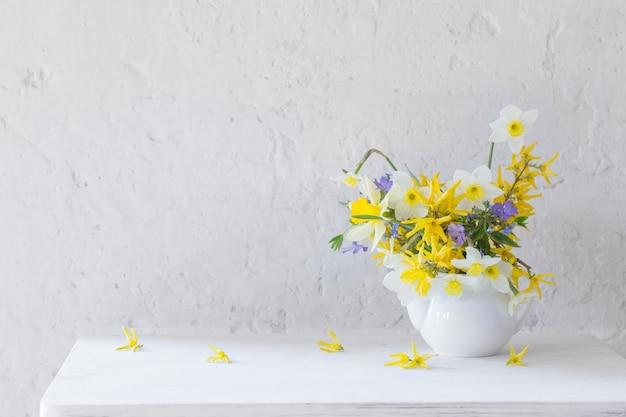 Fiori di primavera bianco e giallo in vaso sulla tavola di legno sulla superficie bianca