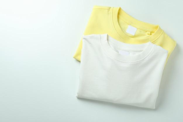 Felpe bianche e gialle su superficie bianca