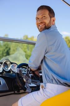 Chi è qui. affascinante giovane seduto al volante di uno yacht e si volta con un sorriso sulle labbra mentre viene chiamato da qualcuno