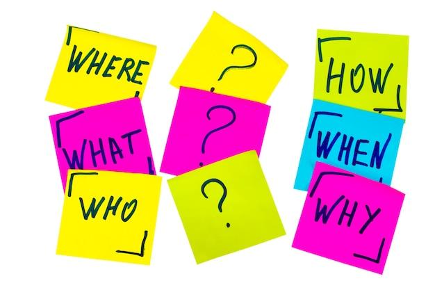 Chi, perché, come, cosa, quando e dove domande: incertezza, brainstorming o concetto di processo decisionale, un insieme di foglietti adesivi colorati isolati.